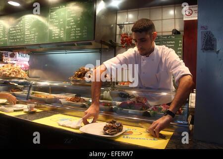 Waiter clearing place setting in bar restaurant in la Boqueria market, Barcelona - Stock Photo