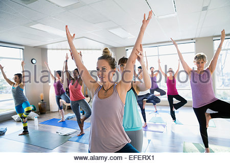 Instructor adjusting students arms in yoga tree pose - Stock Photo