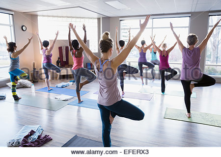 Women practicing tree pose in yoga class - Stock Photo