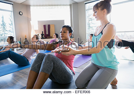 Yoga instructor adjusting students arms in boat pose - Stock Photo