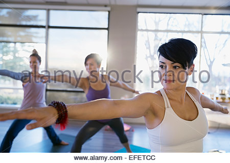 Women practicing warrior 2 pose in yoga class - Stock Photo