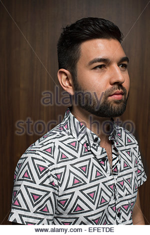 Portrait of pensive bearded man in geometric shirt - Stock Photo