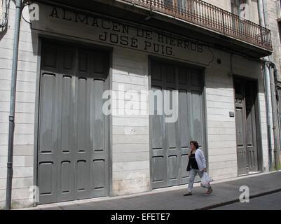 Woman walking along street passed closed store in Girona (Gerona), Catalonia, Spain - Stock Photo