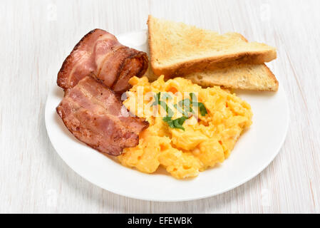 Scrambled eggs with bacon and toasts on white plate, close up view - Stock Photo