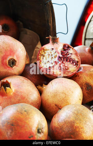 Pomegranate cut open at farmers market sitting on a pile of whole pomegranates - Stock Photo