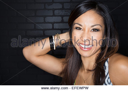Portrait of smiling woman with hand behind head - Stock Photo