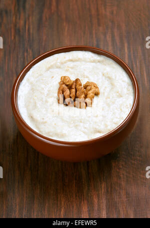 Oatmeal porridge with walnuts in ceramic bowl on wooden table, close up view - Stock Photo