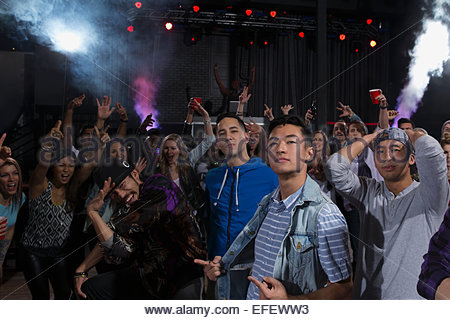 Portrait of confident men among crowd in nightclub - Stock Photo