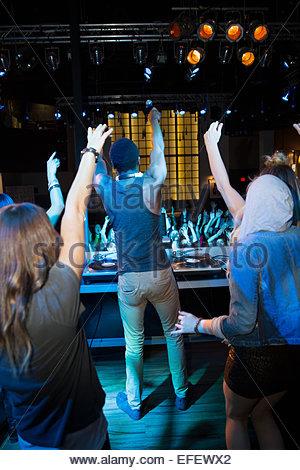 DJ and dancers on stage facing nightclub crowd - Stock Photo