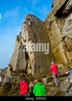Group of climbers watching a friend ascending sheer cliff face on rocks at Curbar Edge Peak District National Park - Stock Photo
