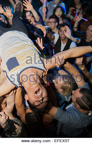 Enthusiastic man crowdsurfing at concert - Stock Photo
