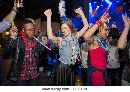 Friends dancing on nightclub dance floor - Stock Photo