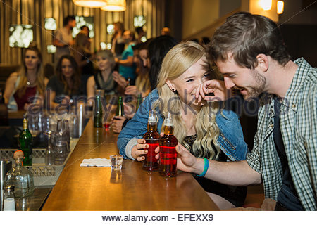 Couple laughing and drinking at bar - Stock Photo