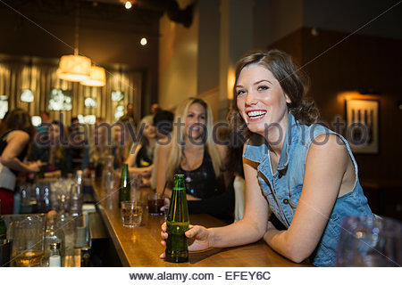 Portrait of smiling woman drinking beer in bar - Stock Photo