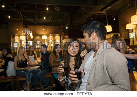 Couple drinking and talking at bar - Stock Photo