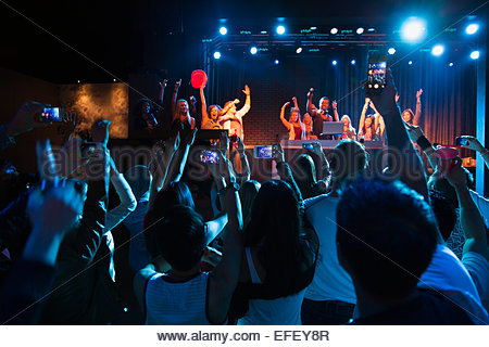 Crowd cheering for DJ and dancers on stage - Stock Photo