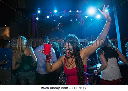 Woman dancing and drinking on nightclub dance floor - Stock Photo