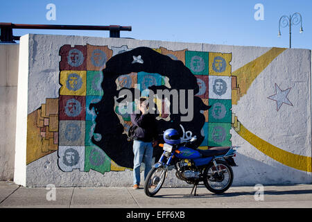 Havana, Cuba. 28th Jan, 2015. A man stands next to his motorbicycle in front of a wall painting which depicts the - Stock Photo