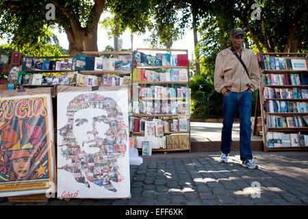 Havana, Cuba. 28th Jan, 2015. A man smokes a cigar as he stands between bookshelves and a poster which depicts the - Stock Photo