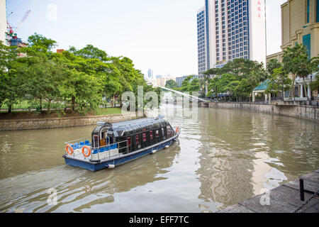 A tourist water taxi boat on Singapore River - Stock Photo