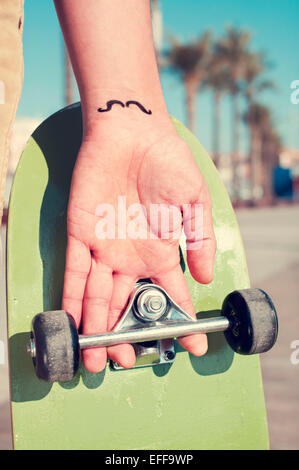 closeup of a young man with a moustache tattooed in his wrist holding a skateboard - Stock Photo