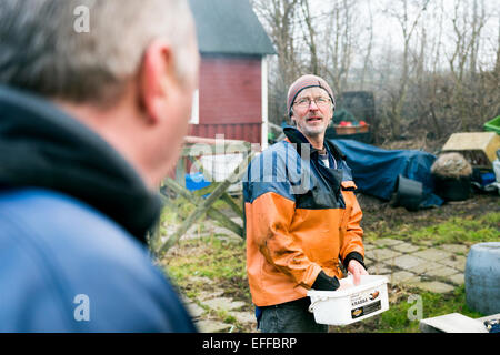 Mature fisherman holding container while talking with colleague outdoors - Stock Photo