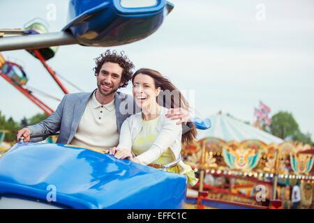 Couple enjoying ride on carousel in amusement park - Stock Photo