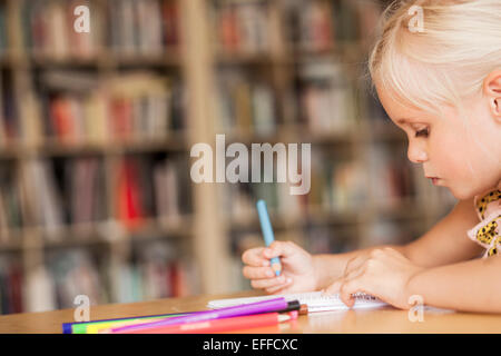 Girl coloring at desk in classroom - Stock Photo