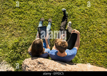 High angle view of couple using digital tablet on grassy landscape - Stock Photo