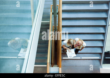 High angle view of students reading book on steps in college - Stock Photo