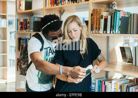 Multiethnic friends reading book in college library - Stock Photo