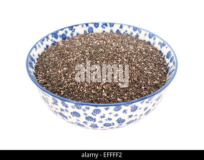 Chia seeds in a blue and white porcelain bowl with a floral design, isolated on a white background - Stock Photo