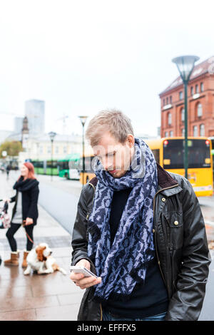 Mid adult man using smart phone on sidewalk while woman standing with dog in background - Stock Photo
