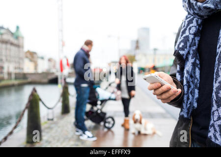 Cropped image of man using smart phone with family in background on sidewalk - Stock Photo
