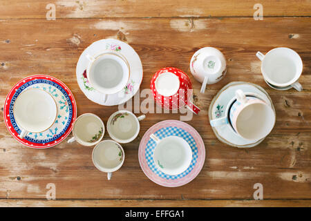Directly above shot of various tea cups and saucers on wooden table - Stock Photo