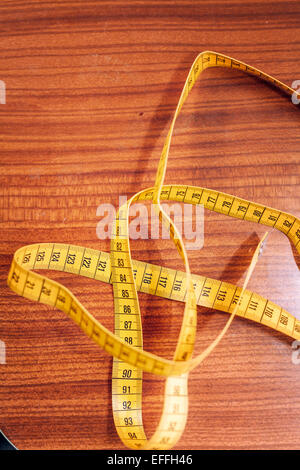 Directly above shot of measure tape on table at workshop - Stock Photo