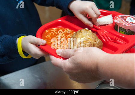 A young child at a UK primary school is handed a school dinner including a jacket potato and spaghetti hoops on - Stock Photo