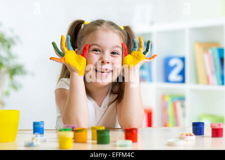 beautiful child girl with hands in color paints - Stock Photo