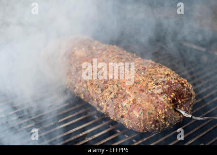 Pork fillet wrapped in bacon on grill - Stock Photo