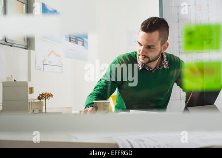 Young man at desk looking at architectural model - Stock Photo