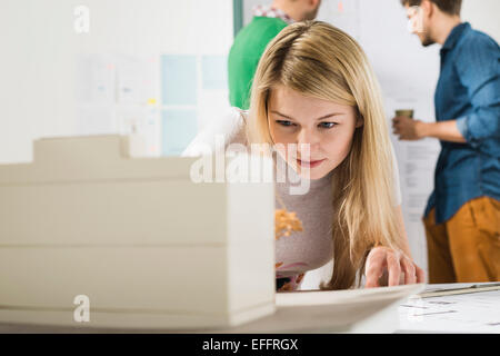 Young woman in office examining architectural model - Stock Photo