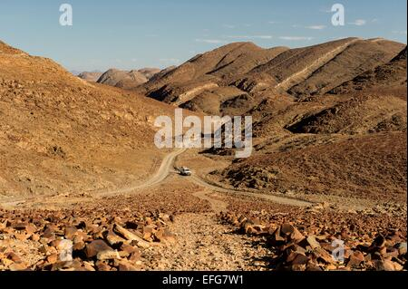 A white 4x4 Toyota Hilux negotiates single tracks in the desert wilderness near Ugab River in western Namibia, Africa. - Stock Photo