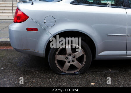 Flat tire on car - USA - Stock Photo