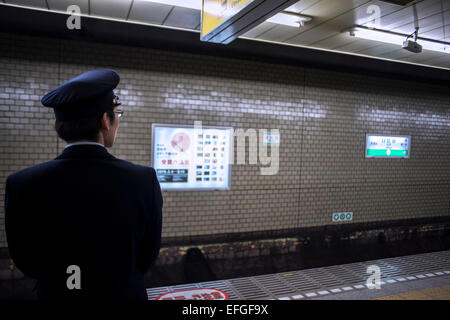 Station crew officer waiting for the train at Hibiya station, Tokyo, Japan - Stock Photo