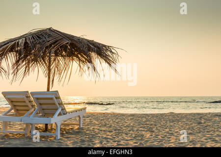 empty chairs under thatched umbrellas on a sandy beach - Stock Photo