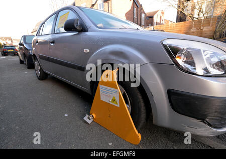 Manchester UK  04th February 2015 A car is clamped on Eversley Road, Didsbury, South Manchester for being untaxed, - Stock Photo