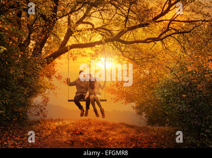 Romantic couple swing in the autumn park - Stock Photo