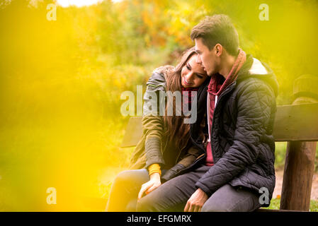 Loving couple in the autumn park sitting on a bench - Stock Photo