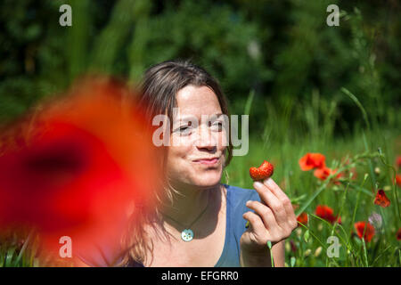 Young woman sitting in a flowering poppy field eating a strawberry - Stock Photo