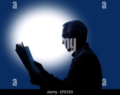 A spot lt background giving a silhouette effect to a man of approximately 60 years old reading a book while wearing - Stock Photo
